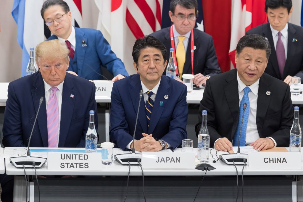 US President Donald Trump (L) sits with Japan's Prime Minister Shinzo Abe (C) and China's President Xi Jinping as they attend a meeting on the digital economy at the G20 Summit in Osaka on June 28, 2019. (Photo by Jacques Witt / POOL / AFP)        (Photo credit should read JACQUES WITT/AFP/Getty Images)