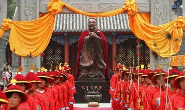 Studenti vestiti in abiti tradizionali onorano Confucio durante una cerimonia nel tempio di Changhun (Jilin) il 25/9/2005. Foto: China Photos/Getty Images