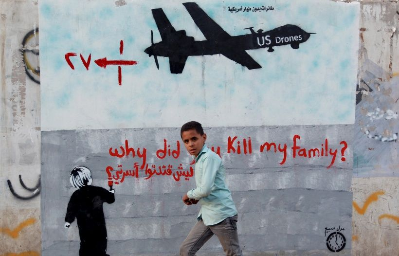 """A Yemeni boy (C) walks past a mural depicting a US drone and reading """" Why did you kill my family"""" on December 13, 2013 in the capital Sanaa. A drone strike on a wedding convoy in Yemen killed 17 people, mostly civilians, medical and security sources said, adding grist to mounting criticism of the US drone war.  AFP PHOTO/ MOHAMMED HUWAIS        (Photo credit should read MOHAMMED HUWAIS/AFP/Getty Images)"""