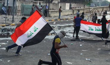 A masked protester runs with an Iraqi national flag amidst clashes with riot police during a demonstration against state corruption and poor services, between the Iraqi capital Baghdad's Tahrir Square and the high-security Green Zone district, on October 1, 2019. - Security forces used water cannons and tear gas to disperse more than 1,000 protesters in central Baghdad. Iraq is considered the 12th most corrupt country in the world according to Transparency International. Power cuts are rampant, water shortages are common and unemployment is high, particularly among youth. (Photo by AHMAD AL-RUBAYE / AFP)        (Photo credit should read AHMAD AL-RUBAYE/AFP/Getty Images)