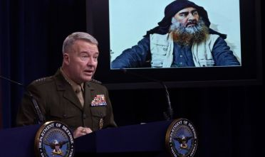 ARLINGTON, VIRGINIA - OCTOBER 30:  U.S. Marine Corps Gen. Kenneth McKenzie, commander of U.S. Central Command, speaks as a picture of  Abu Bakr al-Baghdadi is seen during a press briefing October 30, 2019 at the Pentagon in Arlington, Virginia. Gen. McKenzie and Hoffman spoke to the media to provide an update on the special operations raid that targeted former ISIS leader Abu Bakr al-Baghdadi in Idlib Province, Syria.  (Photo by Alex Wong/Getty Images)