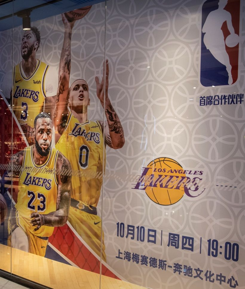 BEIJING, CHINA - OCTOBER 09: A Chinese woman stands next to a billboard showing players from the Los Angeles Lakers and advertising their upcoming exhibition game against the Brooklyn Nets in Shanghai, outside the NBA flagship retail store on October 9, 2019 in Beijing, China. The NBA is trying to salvage its brand in China amid criticism of its handling of a controversial tweet that infuriated the government and has jeopardized the leagues Chinese expansion. The crisis, triggered by a Houston Rockets executives tweet that praised protests in Hong Kong, prompted the Chinese Basketball Association to suspend its partnership with the league. The backlash continued with state-owned television CCTV scrapping its plans to broadcast pre-season games in Shanghai and Shenzhen, and the cancellation of other promotional fan events. The league issued an apology, though NBA Commissioner Adam Silver angered Chinese officials further when he defended the right of players and team executives to free speech. China represents a lucrative market for the NBA, which stands to lose millions of dollars in revenue and threatens to alienate Chinese fans. Many have taken to Chinas social media platforms to express their outrage and disappointment that the NBA would question the countrys sovereignty over Hong Kong which has been mired in anti-government protests since June.(Photo by Kevin Frayer/Getty Images)