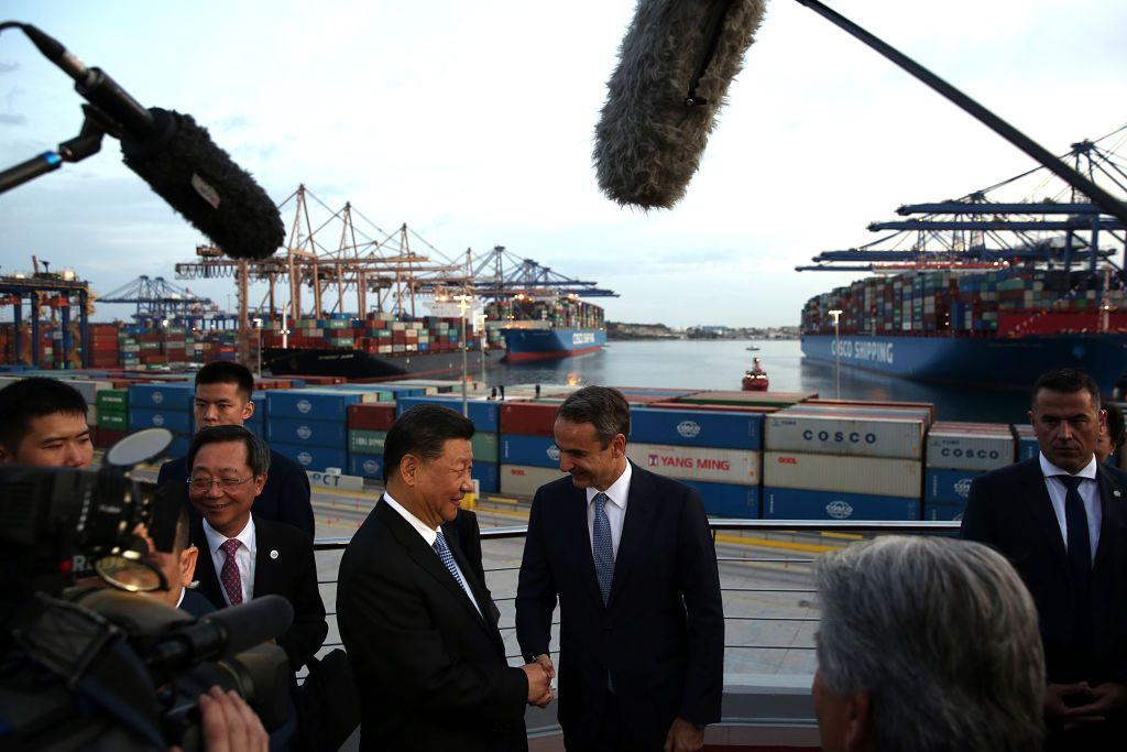 President of the Republic of China Xi Jinping (L) and Greek Prime Minister Kyriakos Mitsotakis (R) shake hands as they visit the cargo terminal of Chinese company Cosco in the port of Piraeus, Greece, on November 11, 2019, as part of his two-day official visit to Greece. (Photo by ORESTIS PANAGIOTOU / POOL / AFP) (Photo by ORESTIS PANAGIOTOU/POOL/AFP via Getty Images)