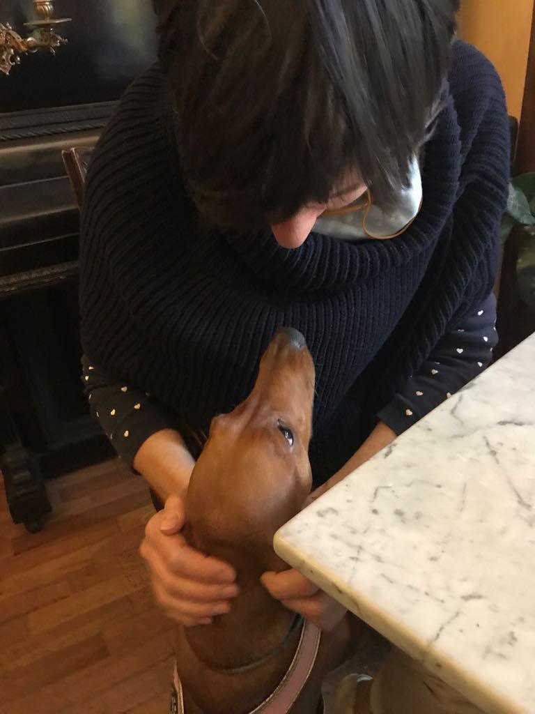 Maria Grazia, il suo cane e, sullo sfondo, un pianoforte