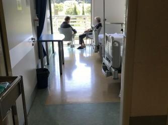Pazienti parlano al sole davanti alla finestra della loro camera