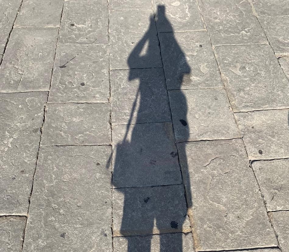 L'ombra di Ginevra sul selciato di una piazza
