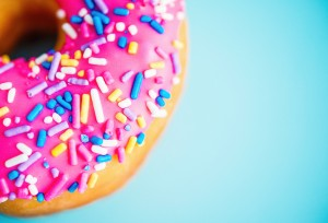 Donut with pink icing and sprinkles on blue background