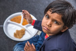 Portrait of Girl kid having mid-day meal in Indian school.