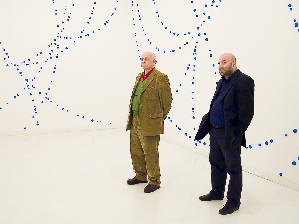 Enrico Crispolti e Gadaleta (con alle spalle una sua opera) alla galleria del Naviglio di Milano