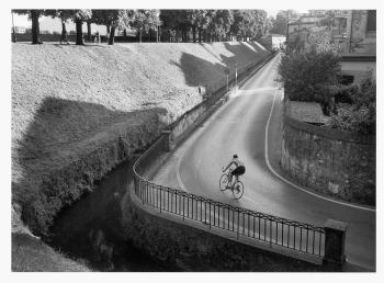 «Lucca, sotto le mura. Senti lo scatto, senti perfino la forza centrifuga che quel ciclista deve compensare facendo la curva. Ecco, queste sono un po' le cose che amo fare, se c'è uno stile mio è qui: un'azione in primo piano, una forma in secondo piano. C'è una foto simile di Cartier-Bresson, non mi fa dispiacere ricordarlo. Le fotografie hanno una vita segreta, parlano fra loro».