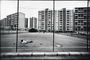 Il quartiere Paolo VI a Taranto, 1995. Sperduto nelle case, in questo quartiere inventato, è l'eterno gioco del pallone che tu vedi, ma un gioco non giocato, con una porta improbabile, una cancellata reale in difesa dall'esterno. Soffocamento, prigionia, anche la porta che è la meta del gioco non c'è, non porta da nessuna parte. Sdraiato in attesa di tempi migliori, se verranno.