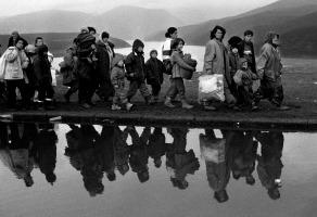 Confine tra Kosovo e Albania, Marzo 1999 Kosovari di etnia albanese abbandonano il loro paese. In questa foto è abbastanza evidente ciò che io definisco il secondo grado. Al primo grado infatti c'è la rappresentazione di un istante mostrato nella sua semplice e drammatica esistenza. Un gruppo di persone di cui scorgiamo un costante sguardo triste e preoccupato, vestite a strati e caricando a braccia, oltre che i bambini più piccoli e deboli, anche buste di altri vestiti e coperte. Sapendo che ci troviamo al confine tra il Kosovo e l'Albania iniziamo a leggere la fotografia nel suo contesto; le persone sono profughi in fuga dalla morte certa e dalle distruzioni degli squadroni della pulizia etnica operanti nei Balcani. Il secondo grado, aggiunto solo dalla lettura simbolica del reale, è un altro specifico che deriva dalla ricco e complesso sviluppo dell'arte pittorica italiana (come nel Quarto stato di Pelizza da Volpedo, ad esempio). In questo caso il secondo grado risiede nel riflesso delle persone che fuggono e che invita alla memoria di un doppio, di una ripetizione di eventi drammatici per i popoli che abitano queste terre.