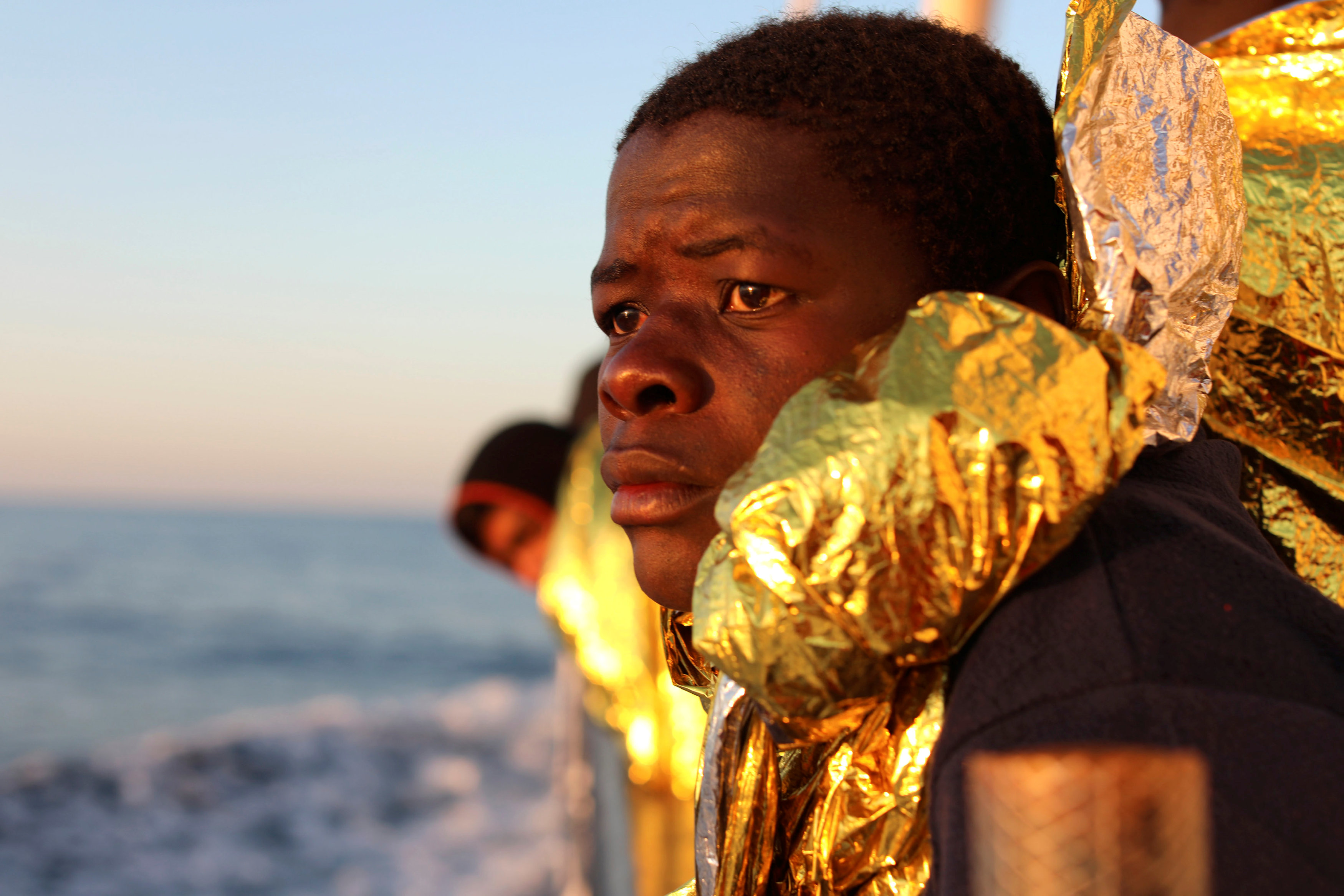 A migrant, covered with a thermal blanket, gazes at the sea aboard the former fishing trawler Golfo Azzurro of the Spanish NGO Proactiva Open Arms following a rescue operation near the coasts of Libya in the central Mediterranean Sea