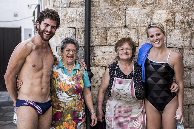 David Colturi (L) and Rachelle Simpson of the USA stop for a photo with two local ladies in the old town during the first training session of the seventh stop of the Red Bull Cliff Diving World Series, Polignano a Mare, Italy on September 11th 2015.