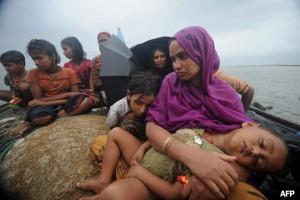 Donne e bambini Rohingya cercano di attraversare il fiume Naf per sfuggire alle violenze
