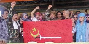 Nur Misuar (al centro) con la bandiera della Repubblica di Bangsamoro