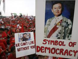 """Manifestazione di camicie rosse con la foto di Thaksin, """"simbolo di democrazia"""""""