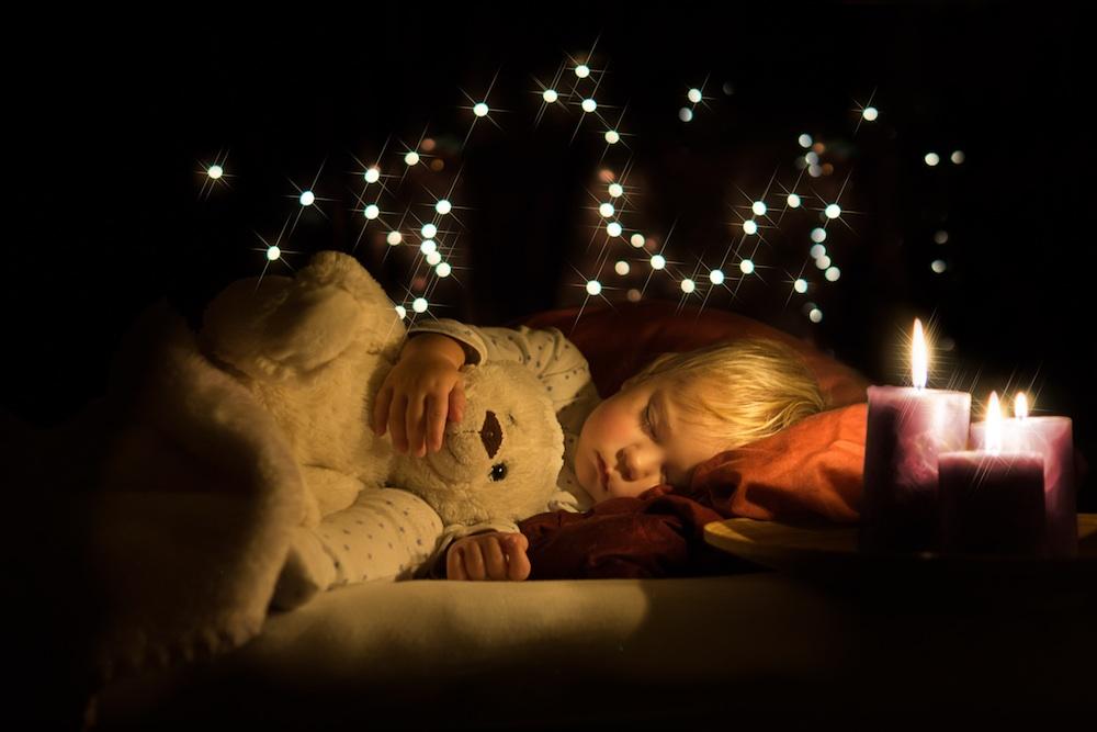 Boy asleep with teddy and warm candle light