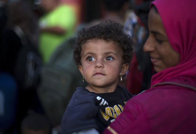 A migrant girl waits with her mother to board a train after crossing the Macedonian-Greek border near Gevgelija