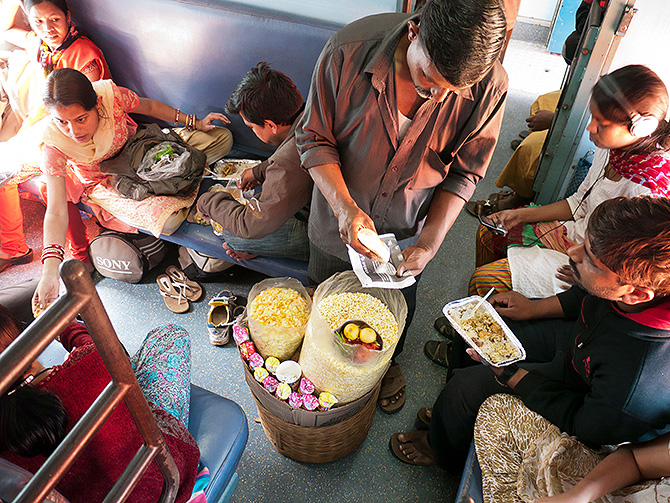 A vendor serving Bhelpuri to passengers on a train in India