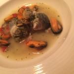 Roll di spigola cotta al vapore con cuore di carcio fi saltati all'aglio e  zuppetta ai frutti di mare