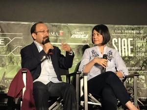 Asghar Farhadi con l'interprete sul palco di piazza San Cosimato