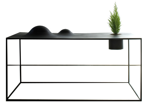 Il tavolo Dune di DeCastelli, in acciaio, contiene piante e ha rilievo che ricorda il paesaggio sabbioso<br><strong>www.decastelli.it</strong>