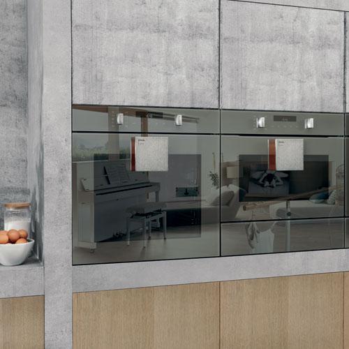 Un dettaglio della cucina Gorenje by Starck: i forni in vetro specchiato che riflettono la rifinitura arancione della maniglia che risalta sull'acciaio inox. Lo speciale design a volta consente un'efficace e uniforme distribuzione del calore e, di conseguenza, una cottura e doratura ottimali