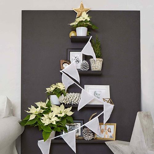 Le decorazioni festive tradizionali come l'albero di Natale possono essere ricreate in chiave moderna utilizzando assi e scaffali da decorare con piante di Poinsettia color crema, foto di famiglia e stelle decorative