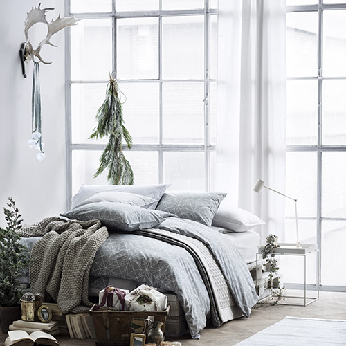 Anche la camera da letto di H&M Home si ispira alla bellezza della stagione invernale: protagonisti i toni del grigio e i tradizionali rami di pino
