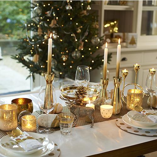 Quest'anno l'oro è il protagonista della casa. La tavola di Dalani smorza l'effetto scintillante di questo colore accostandolo al bianco e a elementi naturali, come i sassi decorati, le pigne e la scelta di tessuti grezzi - quali cotone e lino - per il runner