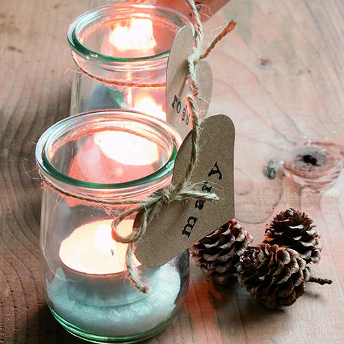 Tra le idee proposte dall'autrice questi piccoli vasetti di vetro che hanno una duplice funzione: segnaposto e portacandele (Shutterstock Images)