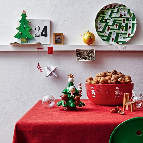 """La tavola di Alessi è divertente grazie ai personaggi disegnati da LPWK - Massimo Giacon: c'è il piatto in ceramica """"Natalino a nascondino"""" con i protagonisti Natalino, Alce, Orson e Hal Freddo all'interno di un labirinto verde, e la ciotola per frutta secca """"Get nuts!"""" con Natalino ritratto mentre lancia noccioline a uno scoiattolo goloso"""