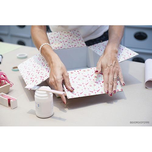 Utilizzando la tecnica del decoupage ricopri l'interno della scatola (fondo e lati) con una carta colorata a tinta unita o fantasia, ritagliando la misura corretta e incollandola con la colla stick