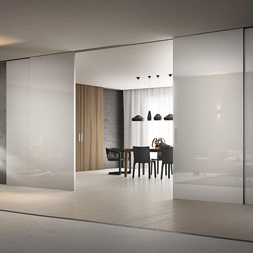 FerreroLegno esalta la teatralità domestica con la parete scorrevole Scenario; qui in foto nella declinazione Premium, con pannelli in vetro tamburato antisfondamento verniciato bianco lucido
