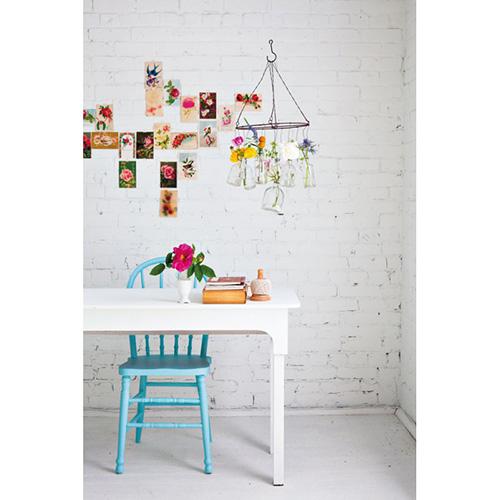 Problemi di budget? In Decorare con i fiori un tutorial per realizzare un lampadario con delle economiche bottiglie di vetro e un robusto fil di ferro