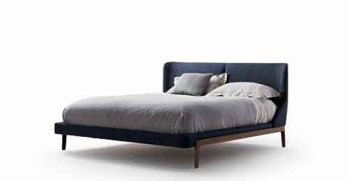 Molteni, Fulham di Rodolfo Dordoni. Un letto con la base in legno e con la testata avvolgente in tessuto o in pelle. In più si può aggiungere una panca ai piedi del letto