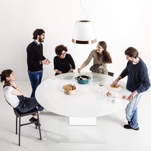 La cucina Air di Daniele Lago per Lago, un tavolo-cucina dove mangiare e cucinare; con piano cottura a induzione e cappa lampadario Summilux di Elica