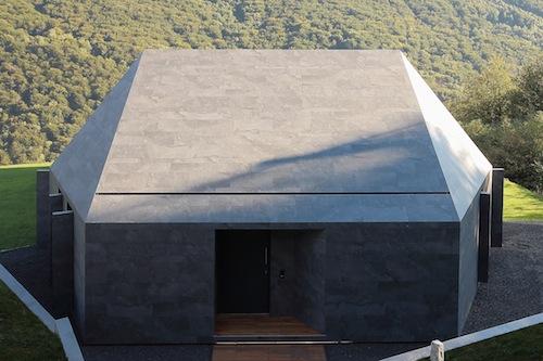 Il progetto è nato partendo dal regolamento edilizio locale che imponeva l?impiego di tetti a falde di color grigio scuro per meglio integrarsi nel paesaggio