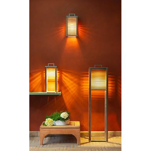 Ginger di Ethimo è disponibile nella versione da terra, da tavolo o da parete. La struttura è in alluminio e il diffusore è realizzato con lamelle in teak