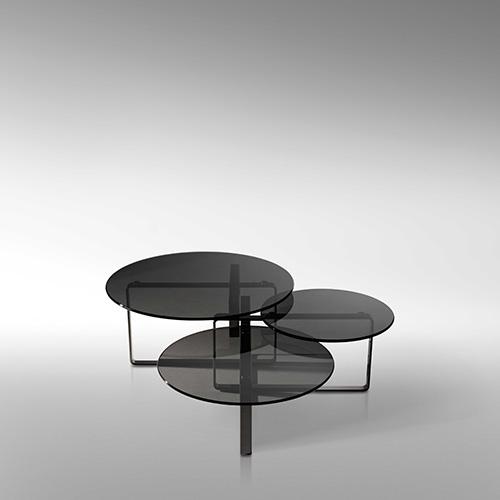 Columbus di Fendi propone un gioco di anelli rettangolari realizzati in piatto d'acciaio cromato scuro e di piani in vetro fumé di diverse dimensioni posti su più livelli, che rendono i tavolini unici a seconda del punto di vista dal quale li si osserva