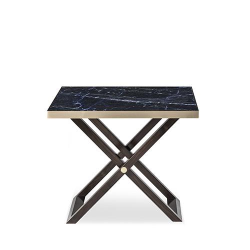 Il tavolino pieghevole è la soluzione ideale per numerose esigenze. Oreste di Armani Casa è anche prezioso poiché accosta il top in pietra solidale blu alla struttura in noce cavallette e ottone