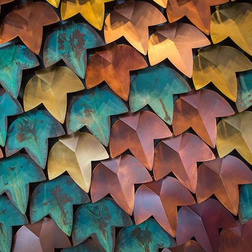 Vertical green  è un rivestimento modulare adatto sia agli interni che agli esterni. Creato da De Castelli, il motivo ricorda le foglie di vite ed evoca un caratteristico scenario autunnale scaldato dalla scelta dal rame e dalle sue finiture: dal bruno-rossastro al bronzo, ai verdi