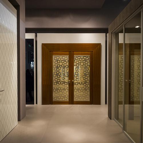 Una porta molto tecnologica di Baurasse, con doppia anta in legno, resistente al fuoco per un'ora e insonorizzata, con rivestimento interno in pelle con applicata una griglia decorativa in acciaio inox, telaio in legno estendibile e coprifilo architettonico largo e sagomato