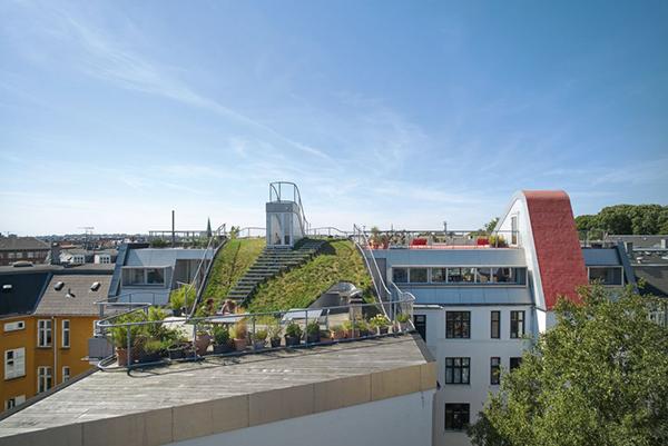 A Copenhagen Julien De Smedt ha realizzato tre attici sui tetti e un'area verde in comune che ospita un parco giochi, una terrazza panoramica di avvistamento, una cucina esterna con barbecue e una piattaforma di legno. Foto di Julien Lanoo