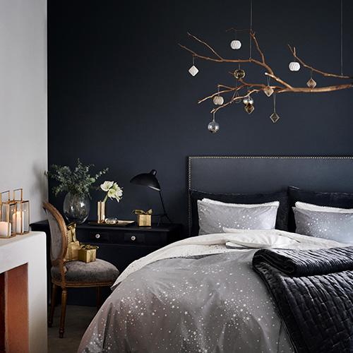 La camera da letto di H&M Home si ispira alla bellezza della stagione invernale: protagonisti i toni del grigio e dell'oro. Le classiche palline di diverse forme e finiture non sono appese su un abete, ma su rami spogli