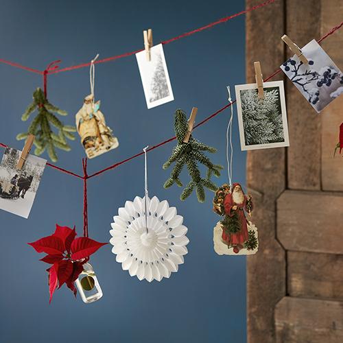Stendere un filo nel salotto o in cucina per appendere, con simpatiche mollette in legno, scatti fotografici ricordo, bigliettini d'auguri, decori, rametti di abete, ramoscelli di ginepro e Stelle di Natale recise