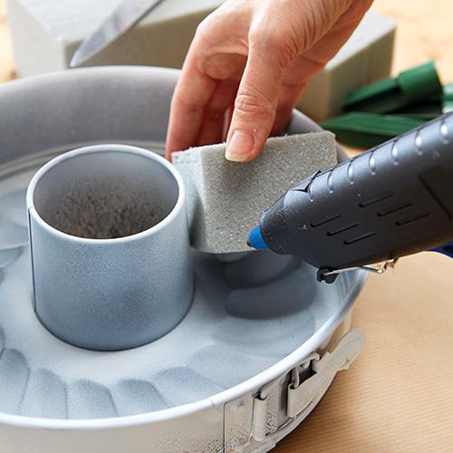 Tagliare quattro blocchi di schiuma da fiorista e sistemarli in modo che siano equidistanti tra loro all'interno della tortiera. Utilizzare la colla a caldo per fissare tutti i pezzi