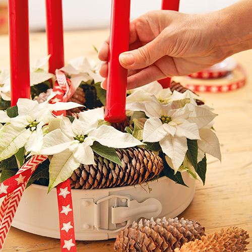 Nascondere la schiuma da fiorista con del muschio e annodare un bel nastro rosso lungo, facendo in modo che scenda da un lato, per rendere il tutto più elegante e natalizio. Tocco finale: inserire le candele all'interno dei candelieri. A piacere aggiungere qualche altro elemento decorativo, come ad esempio delle pigne