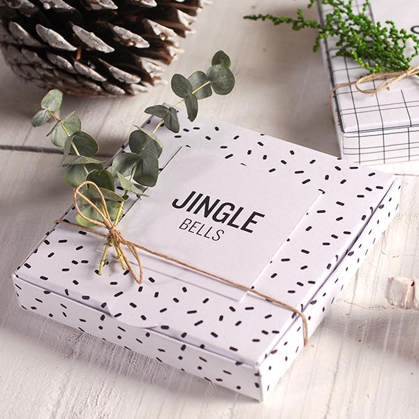 Scatola piatta natalizia con coriandoli stampati, decorata con cordoncino di canapa e un rametto di eucalipto
